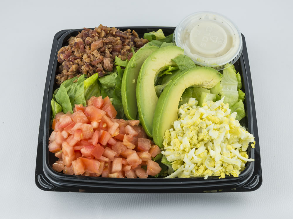Cobb Salad: Sliced avocados, diced tomatoes, bacon pieces, grated eggs, over fresh romaine lettuce with a papaya seed dressing. $6.25